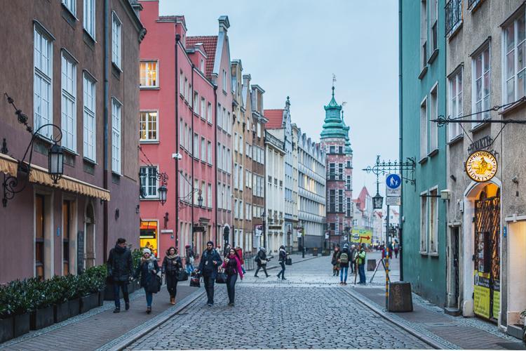 zimowy widok malowniczej brukowanej ulicy Grabary w Gdańsku z widokiem wież Wielkiej Zbrojowni