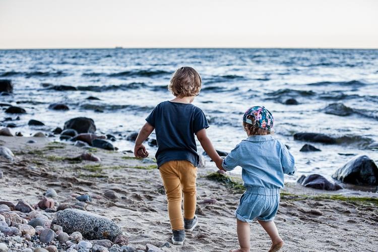 chłopiec i dziewczynka biegną po plaży trzymają się za ręce