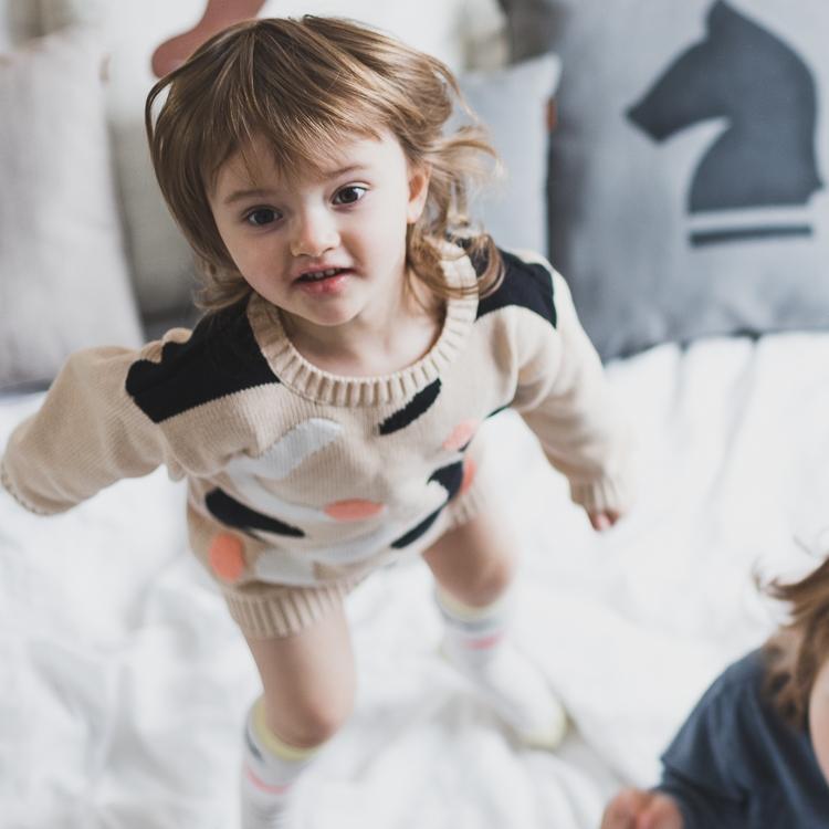 dzieci skaczące po łóżku w sypialni