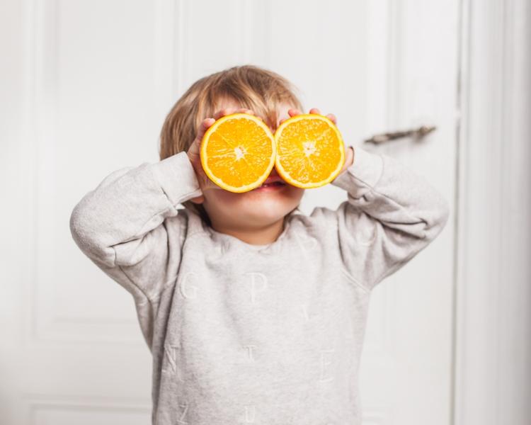 chłopiec pokazuje pomarańczę przekrojoną na dwie części