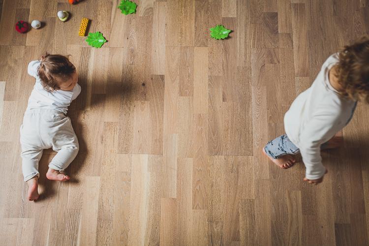 raczkujące dzieci bawią się na drewnianej podłodze mieszkania