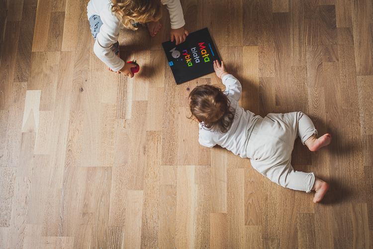 małe dzieci bawią się na drewnianej podłodze w domu