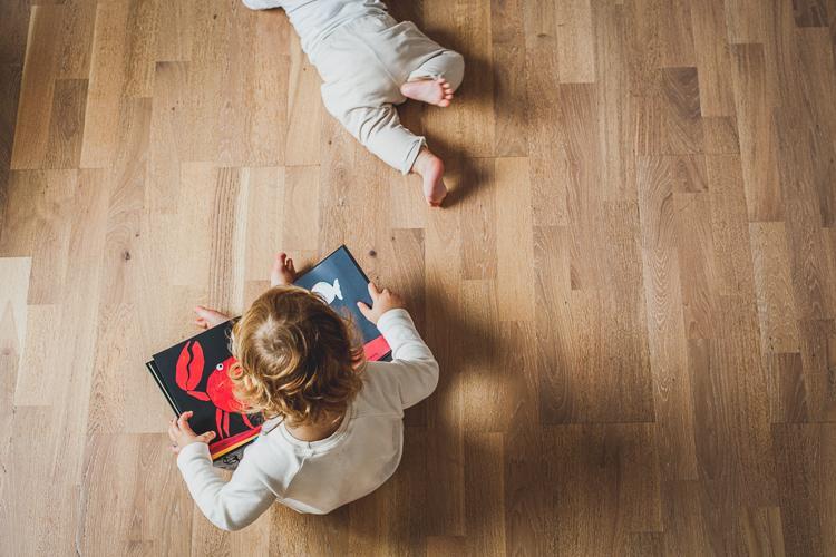 maleńka siostra i brat bawią się na drewnianej podłodze w domu
