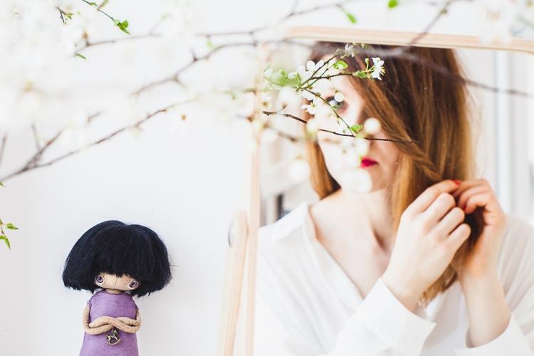 mała lalka totootse przygląda się jak dziewczyna zaplata sobie włosy