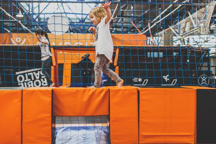 mały chłopiec bawi się na torze przeszkód na trampolinach jump city