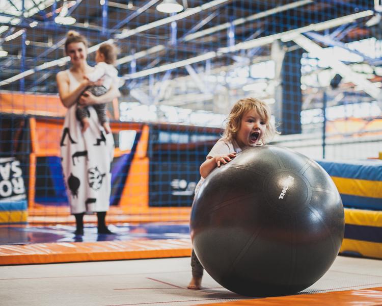 mały chłopiec bawi się z piłką na trampolinach sportowych w jump city w Gdyni