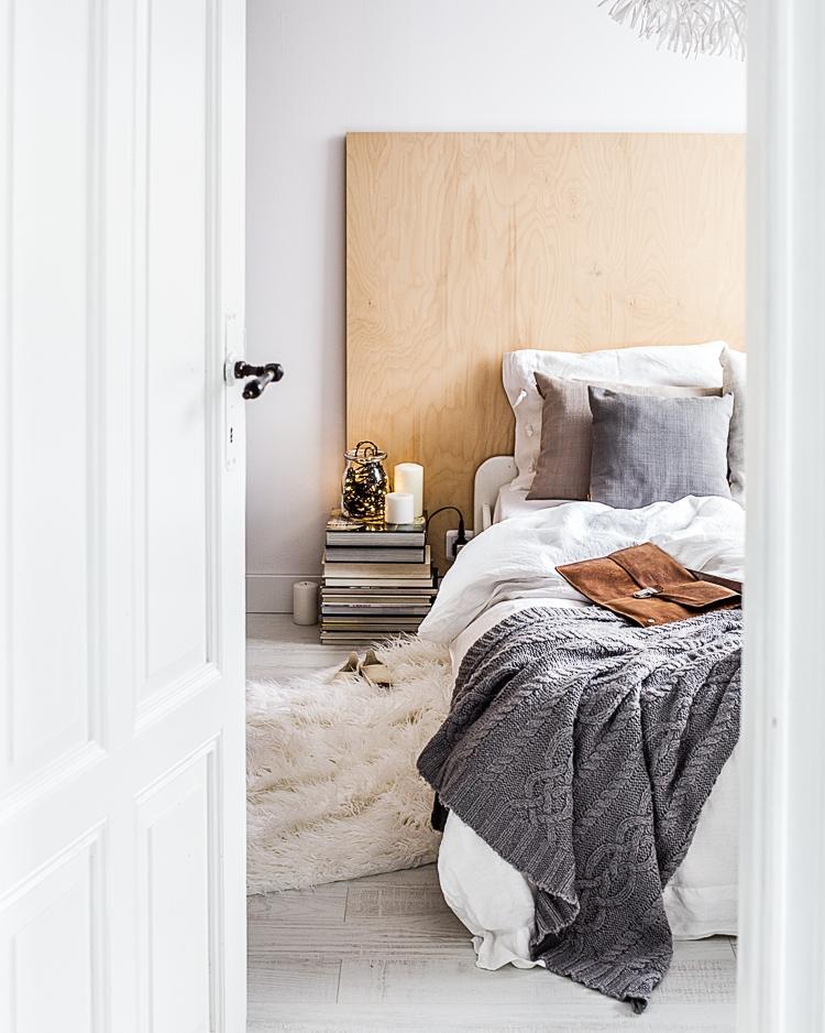 wezgłowie łóżka w sypialni wykonane z płyty drewnianej