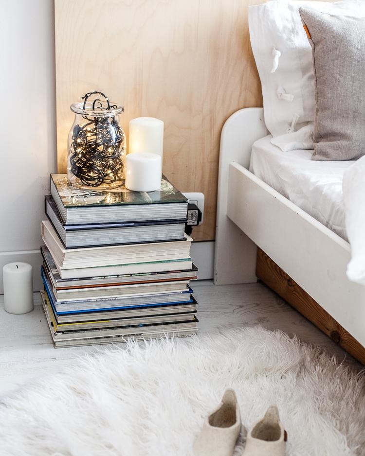 szafka nocna w sypialni wykonana z książek lub albumów
