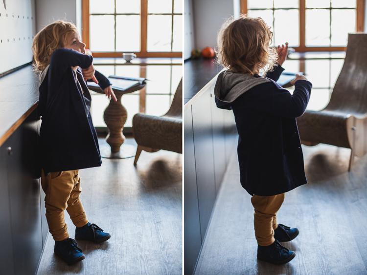chłopiec w żółtych spodniach mon chou i granatowej bluzie stoi przy stoliku w kawiarni