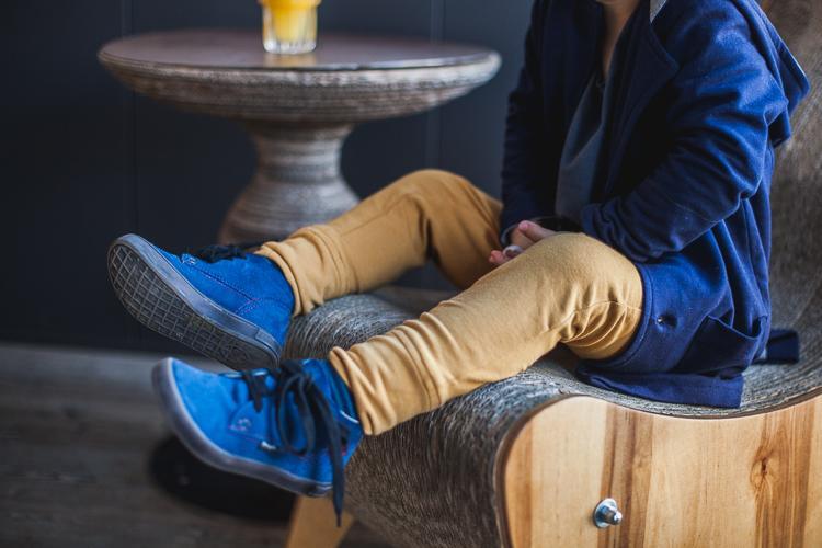 chłopiec w spodniach typu baggy i niebieskich zamszowych butach mrugała