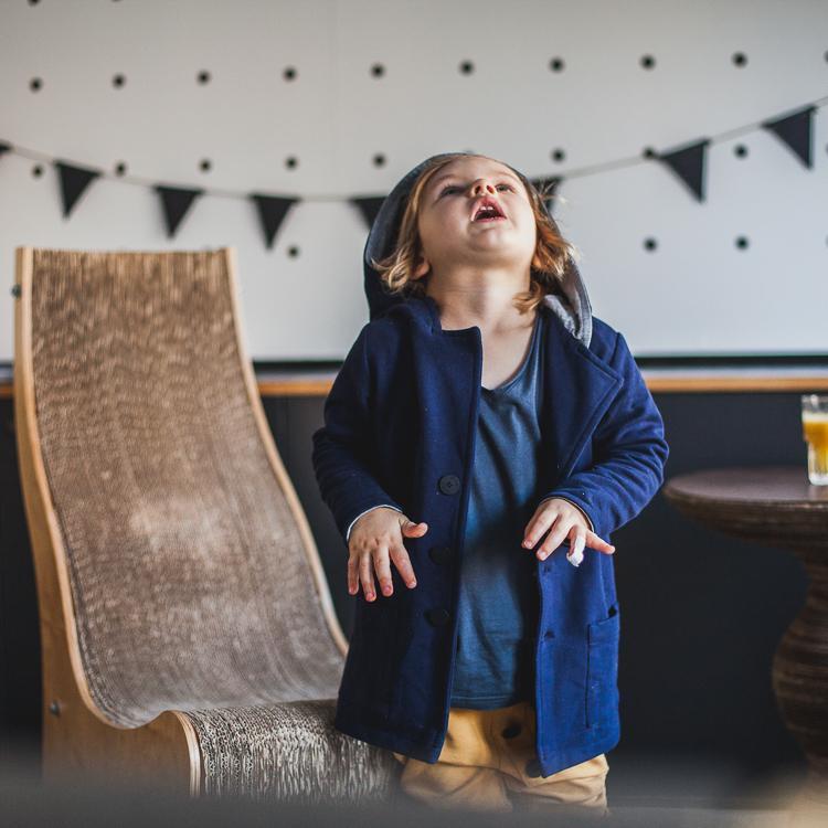 chłopiec ubrany w granatową marynarkę mon chou bawi się w kawiarni drukarnia