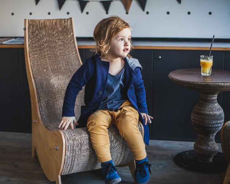 chłopiec ubrany w granatową marynarkę i żółte spodnie mon chou siedzi na fotelu w kawiarni