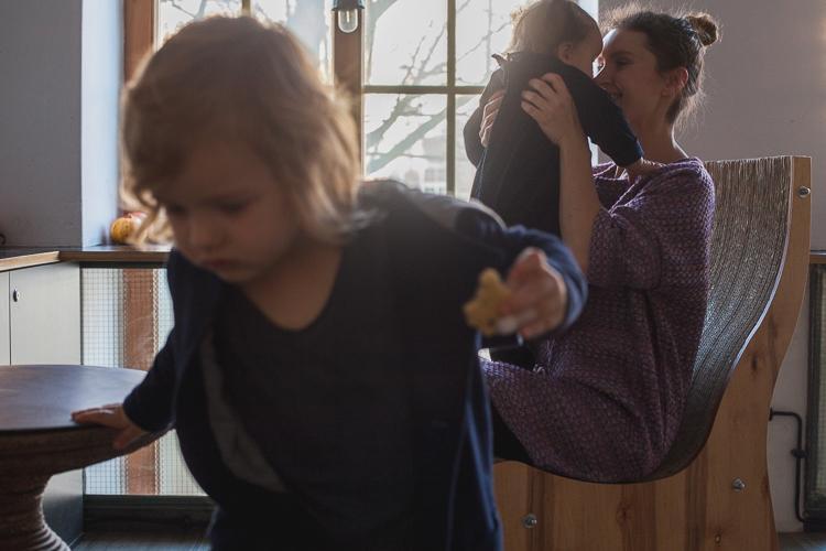 mama przytula maleńką córeczkę a starszy syn bawi się obok
