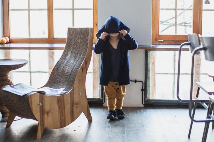 chłopiec ubrany w t-shirt grain de chic i bluzę mon chou zakłada kaptur na głowę