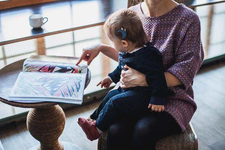 mała dziewczykna ubrana w kombinezon grain de chic bawi się z mamą albumem fotograficznym
