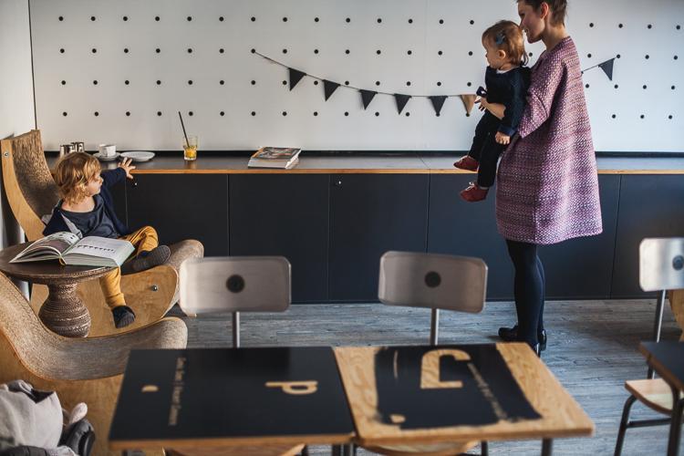 mama ubrana w sukienkę just paul trzyma na rękach córeczkę i rozmawia z synkiem siedzącym na fotelu w kawiarni