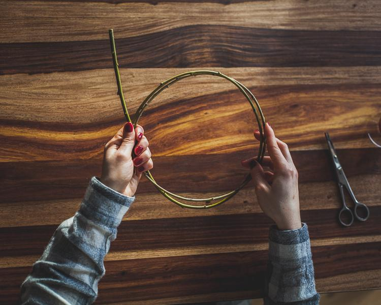 girl making a ring of a willow twig