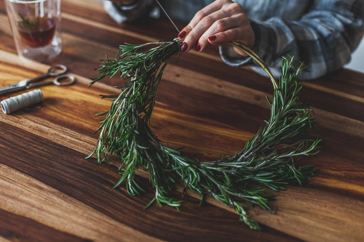 girl fixing rosemary with a stich to a base ring made of willow twig