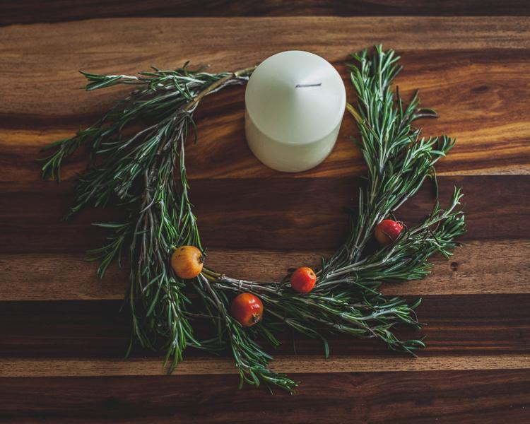 a table decorated with a rosemary wreath with small apples and a white candle