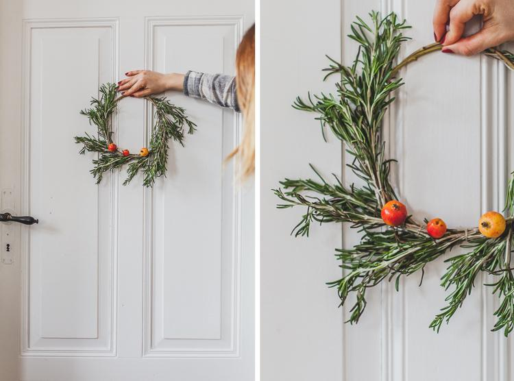 a door decorated with a rosemary wreath with small apples