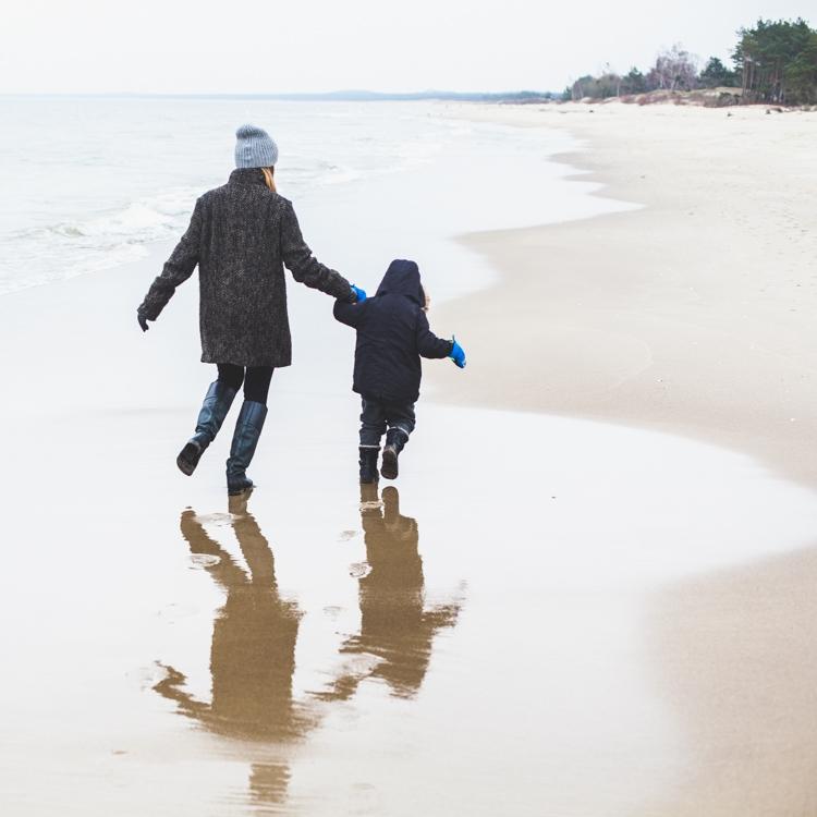 mama biegnie z synkiem po mokrej plaży zimą