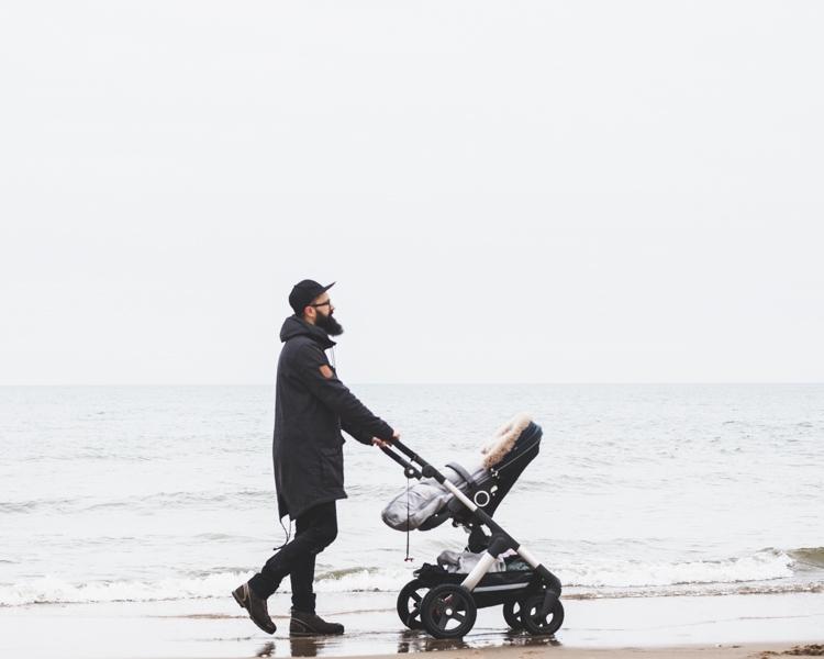 tata spaceruje z wózkiem stokke trailz po plaży zimą