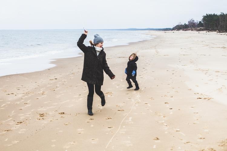 mama puszcza latawca z synem na plaży zimą