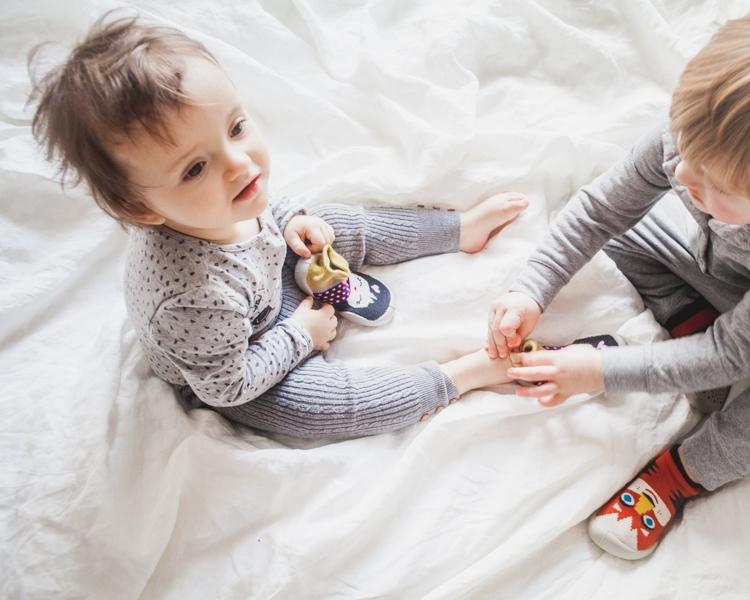 chłopiec zakłada małemu dziecku kapcie