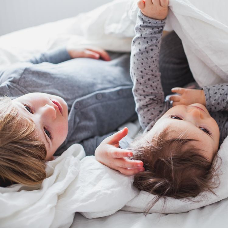 rodzeństwo brat z siostrą leżą na łóżku rodziców ubrani w kapcie dla dzieci
