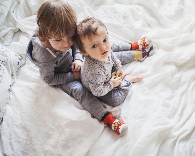 chłopiec z dziewczynką siedzą na łóżku ubrani w kapcie dla dzieci collegien