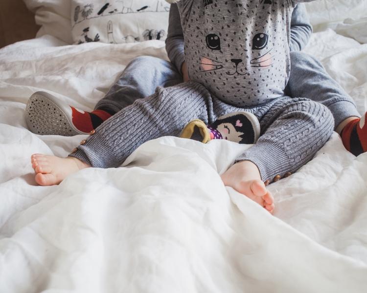 mała dziewczynka siedzi na łóżku w kapciach dla dzieci