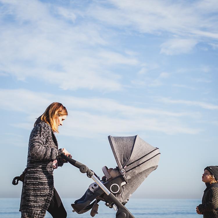 mama spaceruje z córką w wózku trailz oraz starszym synkiem po plaży w Sopocie