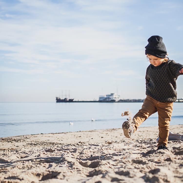mały chłopiec kopie piasek na sopockiej plaży podczas jesiennego spaceru