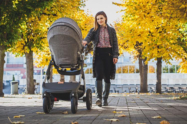 mama spaceruje z córką jadącą  w szarym wózku między jesiennymi drzewami po deptaku przy sopockim Domu Zdrojowym