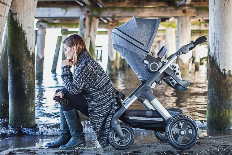 piękna mama z córką w wózku stokke trailz i synem przechodzą pod drewnianą konstrukcją sopockiego molo