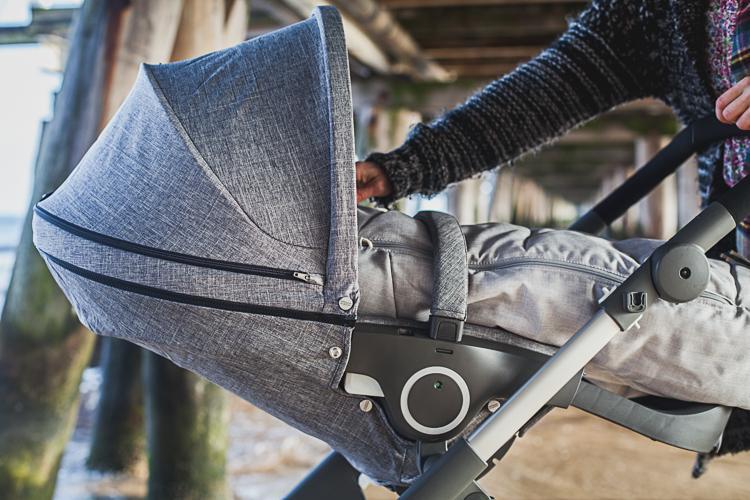 młoda mama poprawia siedzisko wózka stokke trailz przy sopockim molo