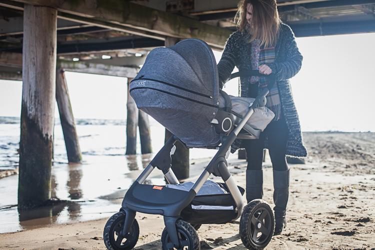 piękna mama z córką w wózku stokke trailz i przechodzi pod drewnianą konstrukcją sopockiego molo