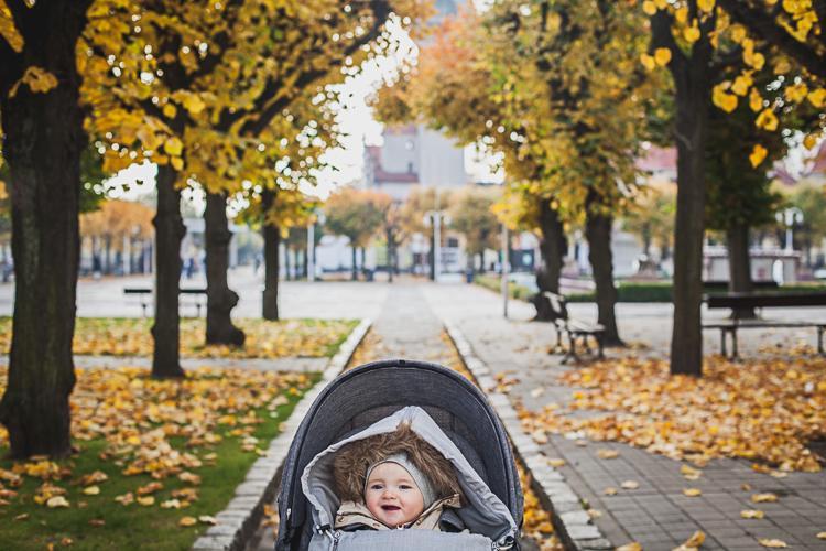 maleńka dziewczynka cieszy się siedząc w wózku stokke w tle jesienna aleja drzew przy sopockim domu zdrojowym