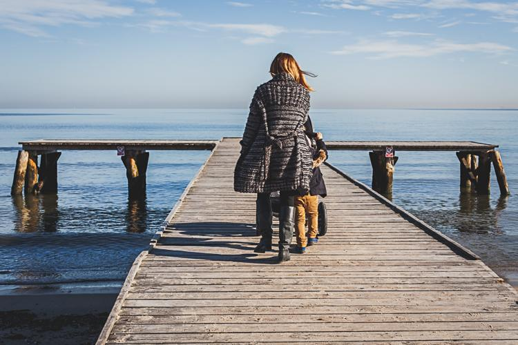 młoda mama z małym synkiem i spacerowym wózkiem trailz spacerują po drewnianym molo w Sopocie