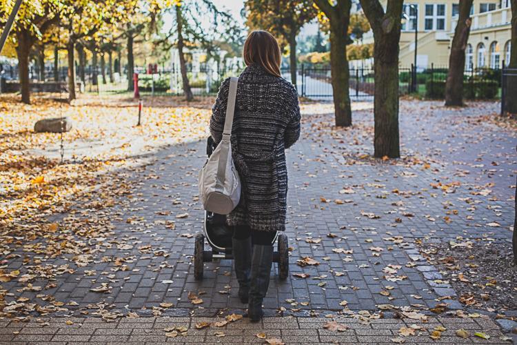 mama spaceruje z wózkiem po ścieżce z kostki w Sopocie
