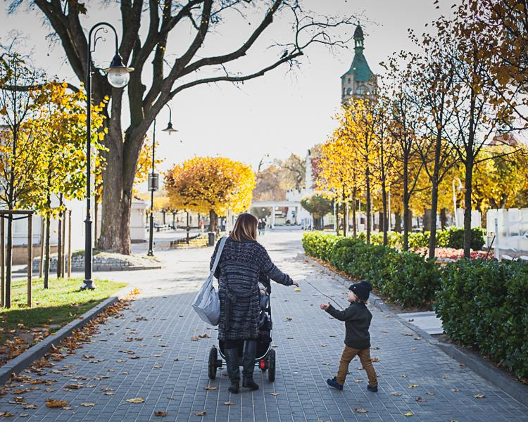 mama i syn spacerują z wózkiem po ścieżce przy plaży w centrum Sopotu