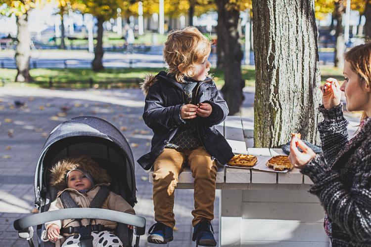 mały chłopiec siedzi na drewnianym stoliku i je gofra obok wózka, w którym siedzi jego młodsza siostra