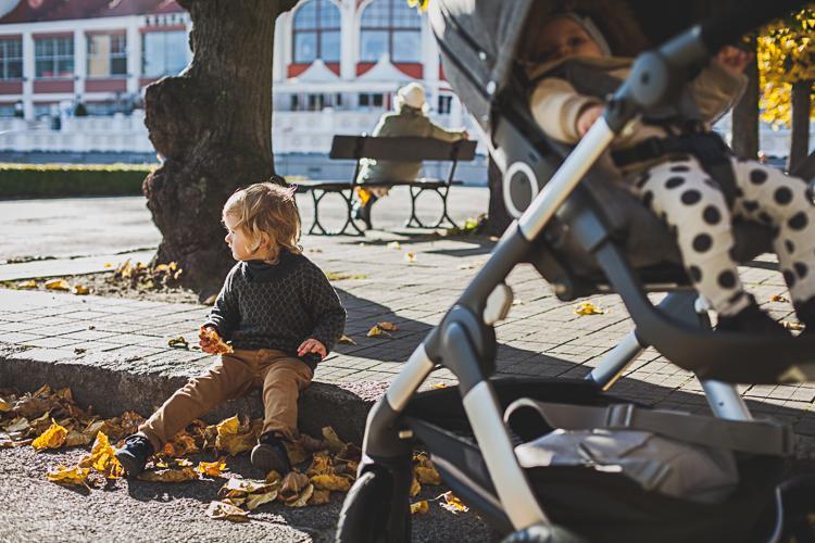 mały chłopiec siedzi na krawężniku i je gofra obok wózka, w którym siedzi jego młodsza siostra