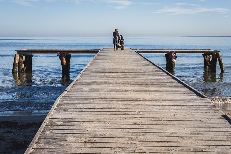 mama z małym synkiem i wózkiem spacerują po drewnianym molo w Sopocie