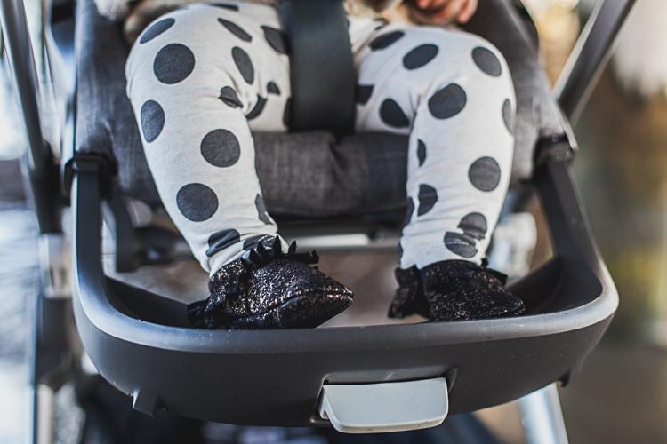 nóżki malutkiej dziewczynki w czarnych skórzanych bucikach siedzącej w wózku trailz stokke