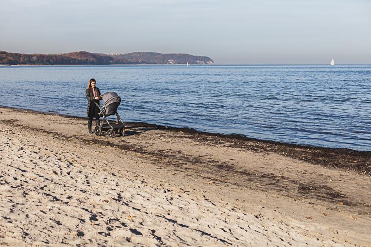 młoda mama z synkiem spacerują po plaży w Sopocie obok stoi spacerowy wózek z młodszą córką