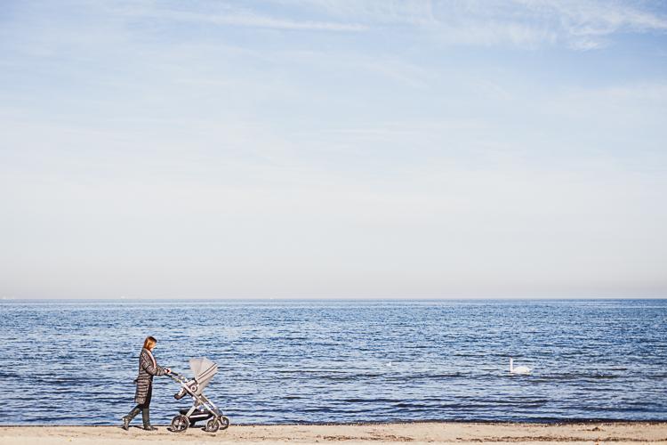 młoda mama spaceruje po plaży w Sopocie prowadząc piękny terenowy wózek stokke trailz
