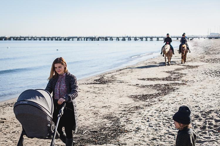 mama idzie po plaży z wózkiem spacerowym stokke a za nią jadą dżokejki na pięknych koniach