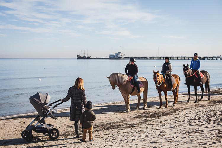 mama z synem podziwia młode dżokejki na plaży w Sopocie