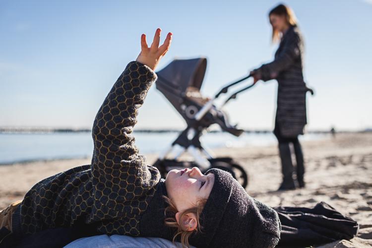 młoda mama spaceruje z córką w wózku trailz po plaży podczas gdy starszy syn odpoczywa leżąc na śpiworku